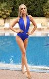 有金发的女孩在游泳衣,松弛近的游泳的po 免版税库存照片