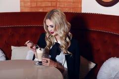 有金发的妇女在典雅的衣服和帽子,坐在咖啡馆用咖啡 库存照片