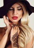 有金发的妇女有晚上构成的和在手上的无刺指甲花纹身花刺 免版税库存图片