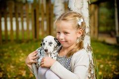 有金发的小女孩使用与在庭院背景的小狗 小女孩拿着在她的胳膊的一只小狗 逗人喜爱的女孩一点 库存照片
