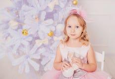有金发的小女孩在桃红色礼服在新年背景中 库存图片