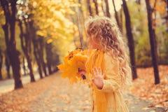 有金发的小女孩在秋天背景中 免版税库存照片