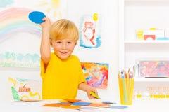 有金发的小男孩和纸板盘旋 免版税库存图片