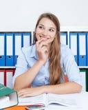 有金发的少妇在解决问题的办公室 免版税库存图片