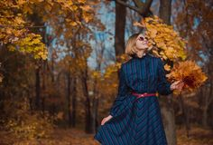 有金发的少妇穿蓝色礼服走在秋天公园的 图库摄影