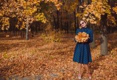有金发的少妇穿蓝色礼服走在秋天公园的 免版税库存照片