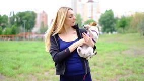 有金发的年轻亭亭玉立的妇女在有她的杰克罗素狗狗的公园,慢动作 股票视频