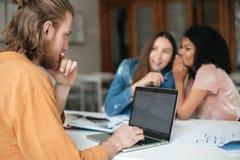 有金发的年轻坐在办公室和研究他的膝上型计算机的人和胡子,当说闲话两个的女孩在背景时 免版税库存照片