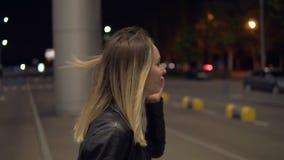 有金发的年轻美丽的妇女走在机场大厦附近的,摆在为照相机,微笑 她佩带 股票录像