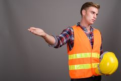 有金发的年轻英俊的人建筑工人反对g 免版税库存照片