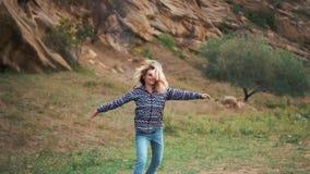 有金发的快乐的年轻女人在宽松蓝色行家衣裳和在她自己附近愉快地旋转在岁月  股票视频