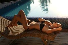 有金发的性感的女孩在摆在游泳池旁边的比基尼泳装 免版税库存照片