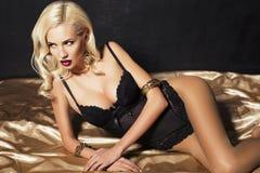 有金发的性感的妇女在女用贴身内衣裤 免版税库存照片