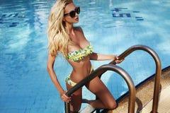 有金发的性感的妇女在摆在游泳池的比基尼泳装和太阳镜 免版税库存照片