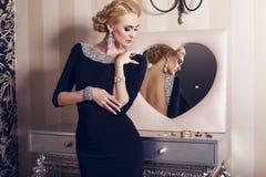 有金发的性感的妇女在有首饰的豪华礼服 免版税库存照片