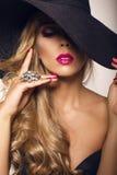 有金发的性感的美丽的女孩在典雅的黑帽会议 库存照片