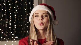 有金发的愉快的无忧无虑的妇女送在圣诞灯背景的一个亲吻 圣诞老人帽子的一美女和 影视素材