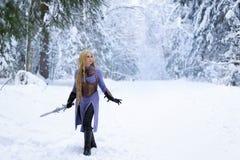 有金发的战士女孩在冬天森林里 免版税库存照片