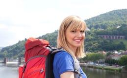 有金发的笑的背包徒步旅行者在欧洲 免版税库存图片