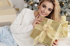 有金发的美丽的女孩在摆在新的Y附近的舒适衣裳 库存照片