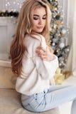 有金发的美丽的女孩在摆在新的Y附近的舒适衣裳 图库摄影
