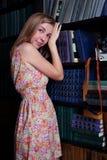 有金发的美丽的女孩在架子旁边站立 免版税库存图片