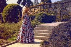 有金发的美丽的妇女在公园的庄重装束 免版税图库摄影