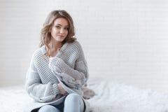有金发的美丽的妇女在灰色在灰色背景的一间明亮的卧室编织了毛线衣 图库摄影