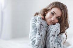 有金发的美丽的妇女在灰色在灰色背景的一间明亮的卧室编织了毛线衣 库存照片