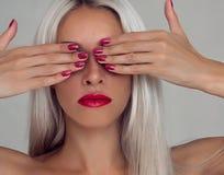 有金发的美丽的妇女 与红色唇膏和红色钉子的时装模特儿 免版税库存图片