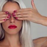 有金发的美丽的妇女 与红色唇膏和红色钉子的时装模特儿 库存图片