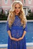 有金发的美丽的孕妇在典雅的鞋带礼服 库存照片