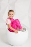 有金发的美丽的小女孩,在白色背景的桃红色总体 免版税图库摄影
