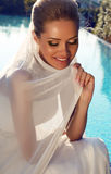 有金发的美丽的微笑的新娘在典雅的婚礼礼服 免版税库存图片
