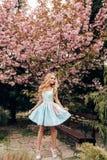 有金发的美丽的肉欲的妇女在摆在有开花的佐仓树庭院里的典雅的衣裳 免版税库存图片