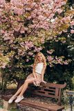 有金发的美丽的肉欲的妇女在摆在有开花的佐仓树庭院里的典雅的衣裳 库存图片