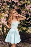 有金发的美丽的肉欲的妇女在摆在有开花的佐仓树庭院里的典雅的衣裳 图库摄影