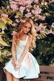 有金发的美丽的肉欲的妇女在摆在有开花的佐仓树庭院里的典雅的衣裳 免版税图库摄影