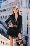 有金发的美女在典雅的成套装备走由春天城市街道的 免版税库存图片