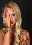 有金发的肉欲的妇女有在手上的无刺指甲花纹身花刺的 库存照片