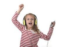 有金发的跳舞甜的小女孩听到与耳机和手机的音乐唱歌和愉快 库存图片