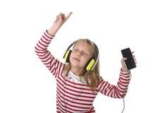有金发的跳舞甜的小女孩听到与耳机和手机的音乐唱歌和愉快 免版税库存图片
