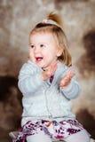有金发的逗人喜爱的小女孩坐椅子和笑 库存照片