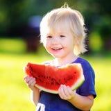 有金发的逗人喜爱的小男孩吃新鲜的西瓜的 免版税库存图片