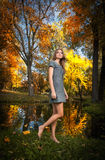 有金发的年轻俏丽的妇女花费时间的在秋季公园。长的有走的腿肉欲的金发碧眼的女人在森林里 库存图片