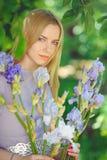 有金发碧眼的女人的可爱的女孩dren嗅到在背景的头发和自然构成蓝色紫色虹膜花户外,嫩 库存图片