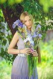 有金发碧眼的女人的可爱的女孩dren嗅到在背景的头发和自然构成蓝色紫色虹膜花户外,嫩 免版税库存图片