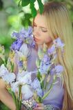 有金发碧眼的女人的可爱的女孩dren嗅到在背景的头发和自然构成蓝色紫色虹膜花户外,嫩 免版税库存照片