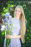 有金发碧眼的女人的可爱的女孩dren嗅到在背景的头发和自然构成蓝色紫色虹膜花户外,嫩 库存照片