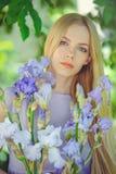 有金发碧眼的女人的可爱的女孩dren嗅到在背景的头发和自然构成蓝色紫色虹膜花户外,嫩 免版税图库摄影